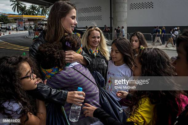 Kids from the Cantagalo 'favela' community rush to hug Caminhos Manager Nadine Leptich thanking her for the Olympic tickets outside the Olympic rugby...