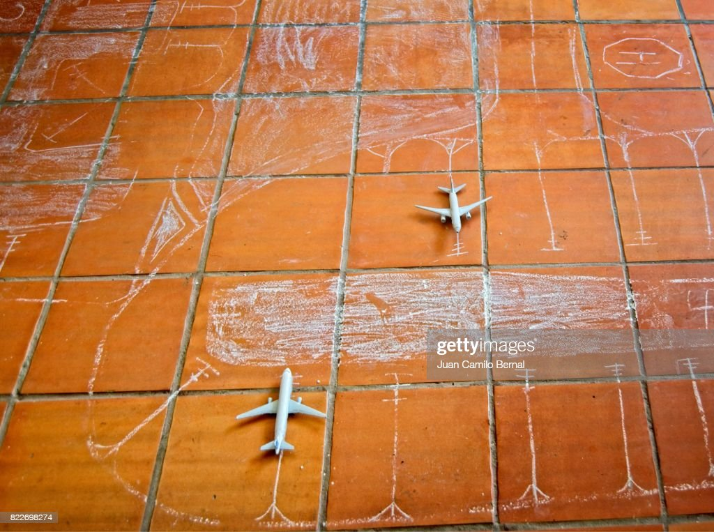 Kids game representing an airport, with small airplanes on a tiled floor : Stock Photo
