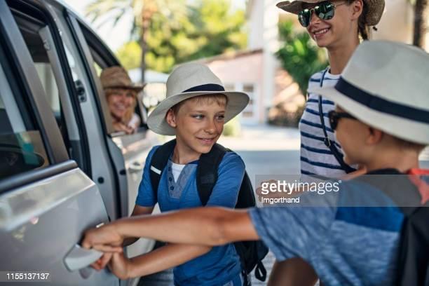 kinder steigen in familienauto für einen road trip - einsteigen stock-fotos und bilder