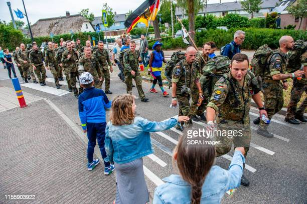 Kids give out candies to Germany soldiers during the event. The Four Days Marches are a walking achievement event for four consecutive days, in which...
