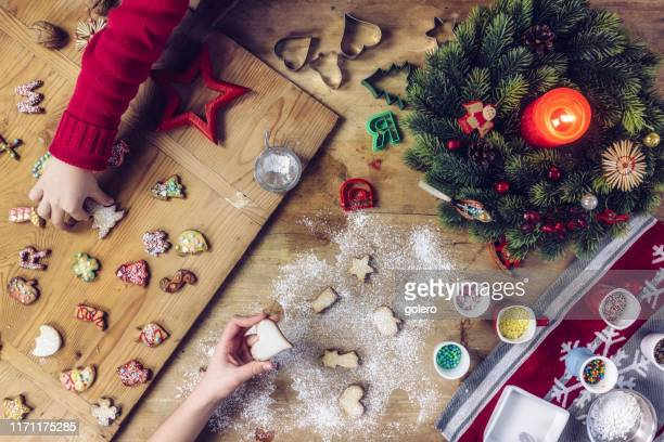 kids hands decorating christmas cookies together - fotosession stock photos and pictures