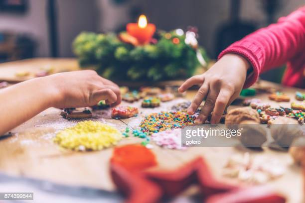 kids hands decorating christmas cookies together - christmas cookies stock pictures, royalty-free photos & images
