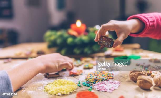 mains d'enfants décorer des biscuits de Noël ensemble