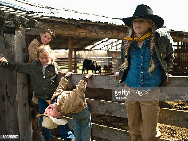 kids hanging out on fence - ranch stock pictures, royalty-free photos & images