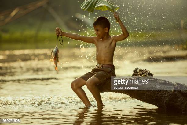 kids have fun with fishing in the river. - fish love stock photos and pictures