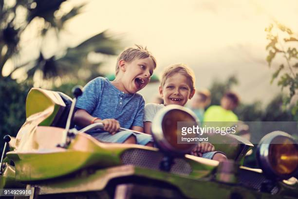 Kids having extreme fun in amusement park roller coaster