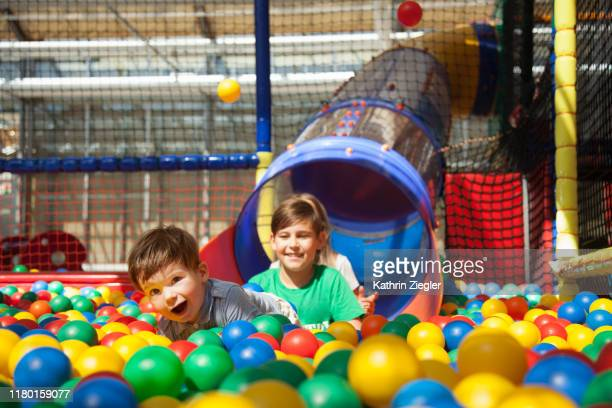 kids having fun at indoors playground, playing with multi colored plastic balls - slide play equipment stock pictures, royalty-free photos & images