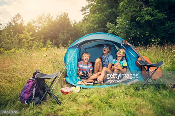 kids having fun camping in tent on the forest meadow - camping stock photos and pictures