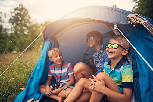 Kids having fun camping in tent on the forest meadow 944545918