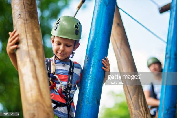 Kids having fun during ropes course in adventure park