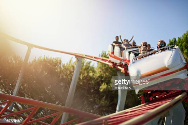 kids having fun in amusement park roller coaster during covid-19 pandemic - amusement park stock pictures, royalty-free photos & images
