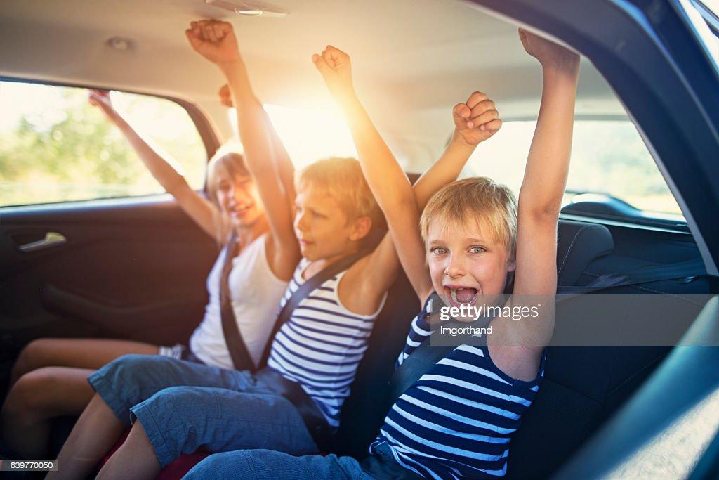 Kids having fun in car on a road trip : Stock Photo