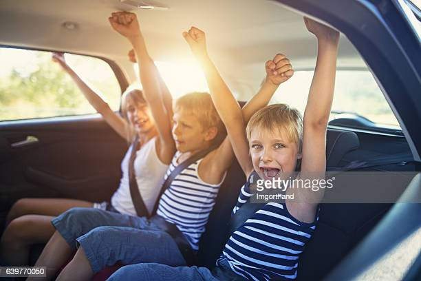 kids having fun in car on a road trip - family inside car stock photos and pictures