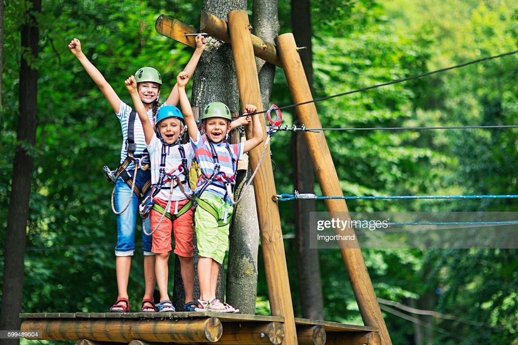 Kids having fun in ropes course adventure park : Foto de stock