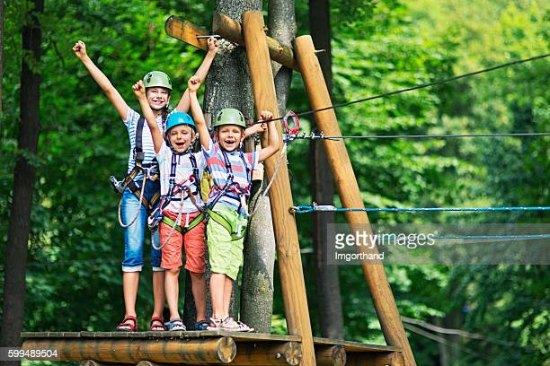 kids having fun in ropes course adventure park - avontuur stockfoto's en -beelden