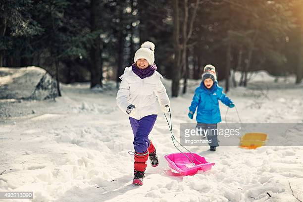 Kids having fun in winter - running with sleds