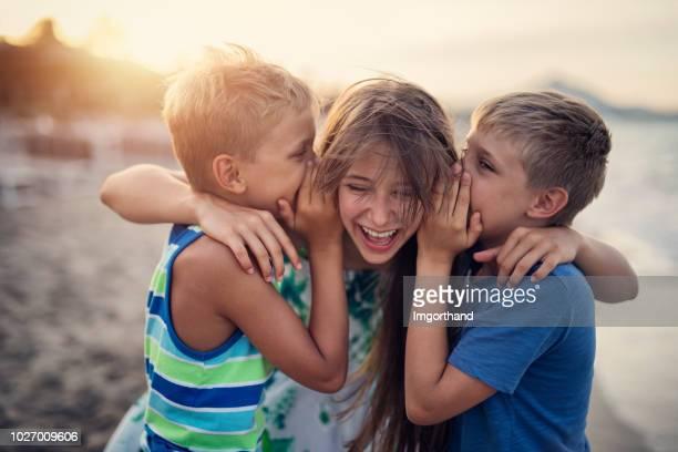 kinder, die spaß am strand sonnenuntergang - nur kinder stock-fotos und bilder