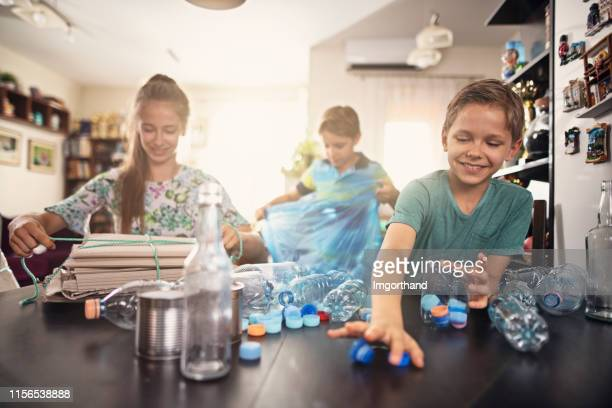 kids having fun segregating waste - recycling stock pictures, royalty-free photos & images