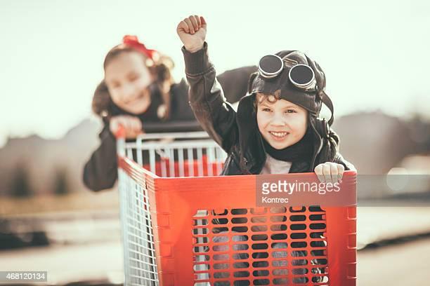 Kinder, die Spaß mit Einkaufswagen