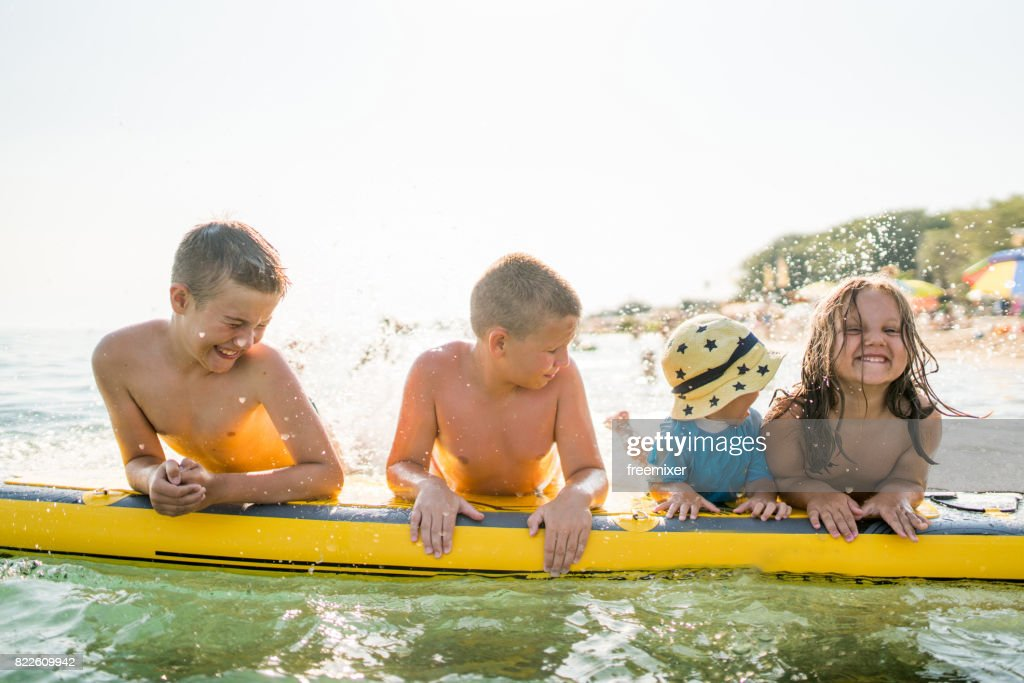 Kids having fun with surfboard : Stock Photo