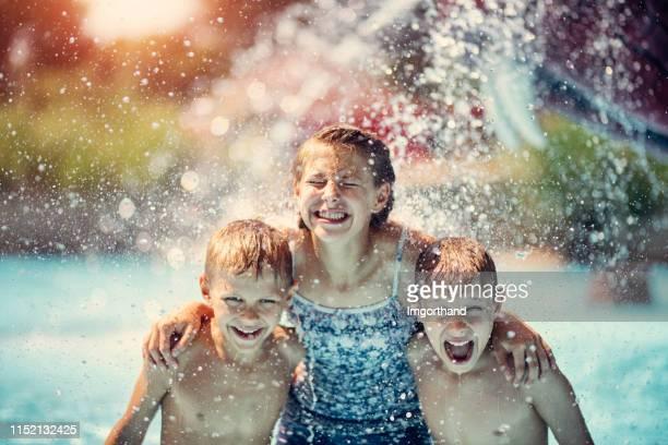gosses ayant éclaboussant l'amusement dans le parc aquatique - fille sous la douche photos et images de collection