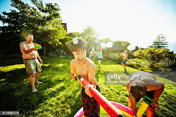 Kids having water fight in backyard with dad