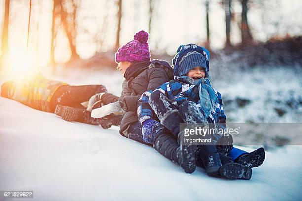 Kids having winter fun sliding on snow