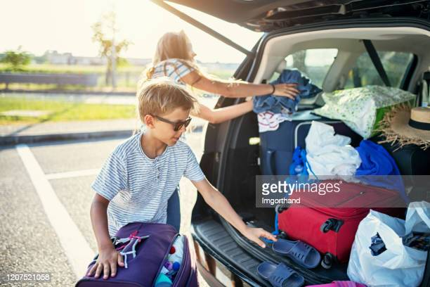 kids helping to pack the family car for road trip. - packing stock pictures, royalty-free photos & images