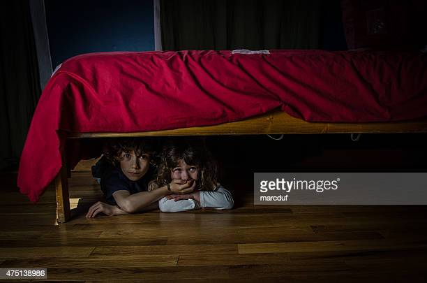 Kids hidden under the bed with fear and crying