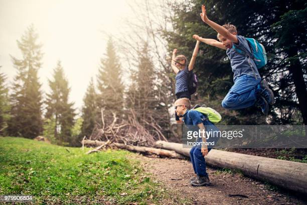 Kids hikers jumping in forest