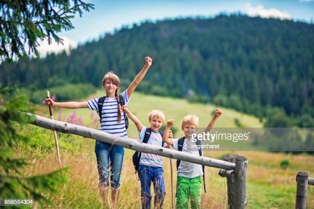 Kids hiking in the grassy field