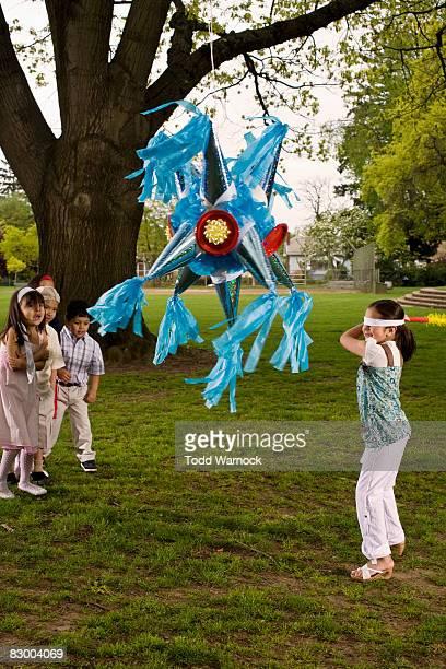 Kinder schlagen Piñata im park