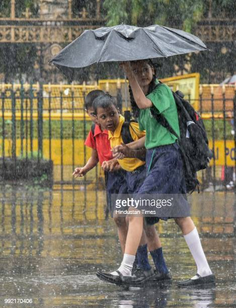 Kids hold umbrella as it rain at CSMT on July 4 2018 in Mumbai India Heavy rains made a comeback in Mumbai causing waterlogging in many parts of the...
