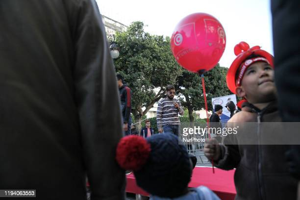 Kids holding red balloons attend a rap show performed by young Tunisian artists on avenue Habib Bourguiba in the capital Tunis during the...
