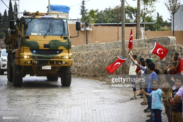 Kids holding Turkish flags are seen as Turkish Army's armoured vehicles are deployed to the Reyhanli border due to the transition to Idlib deconflict...