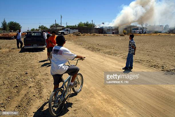 Kids in a Lost Hills neighborhood watch a house fire from the unpaved streets that are common in the town, Friday afternoon, July 23, 2004. ––...