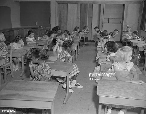 Kids in classroom on the first day of desegregation in Virginia, 1959. (Original Caption reads: 'A Negro child and a white child face each other on...