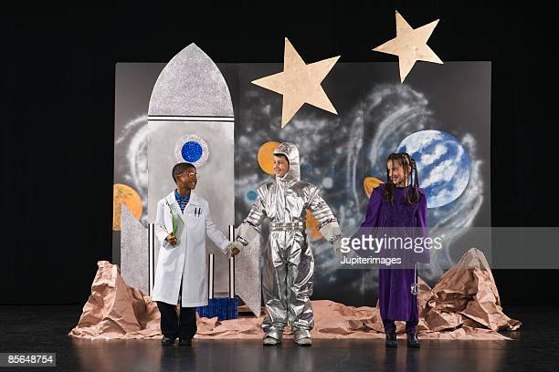 Kids in costume on stage holding hands