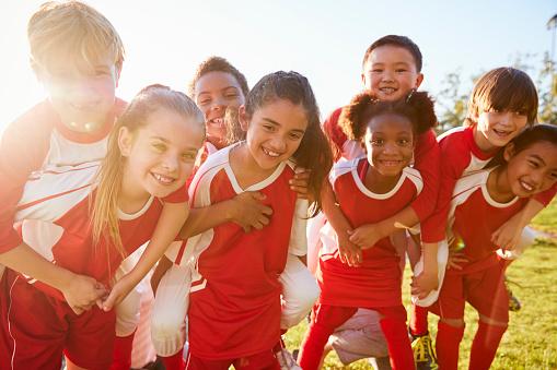 Kids in elementary school sports team piggybacking outdoors 1031366278