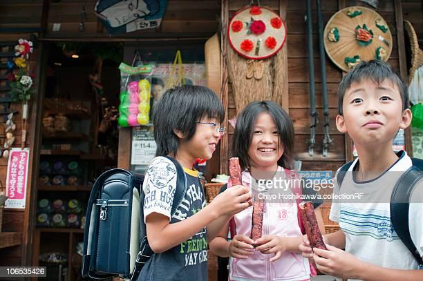 Kids in front of Dagashi-ya eating snacks, Japan