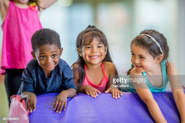 kids in gym class - little girls doing gymnastics stock photos and pictures