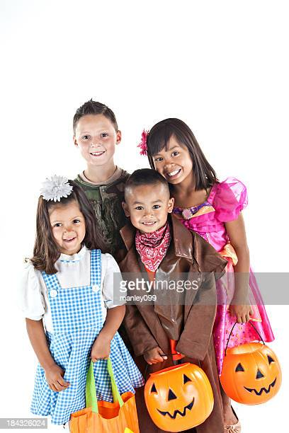 Kids in halloween costumes standing together and smiling