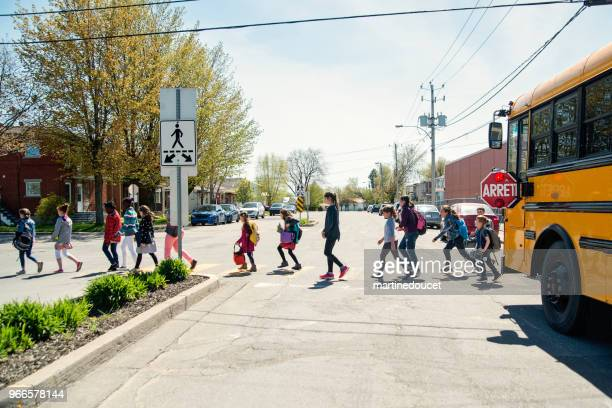 kids in line crossing street getting out of school bus. - quebec stock pictures, royalty-free photos & images