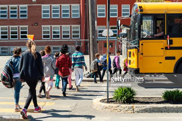 "kids in line crossing street to get on school bus. - ""martine doucet"" or martinedoucet stock pictures, royalty-free photos & images"