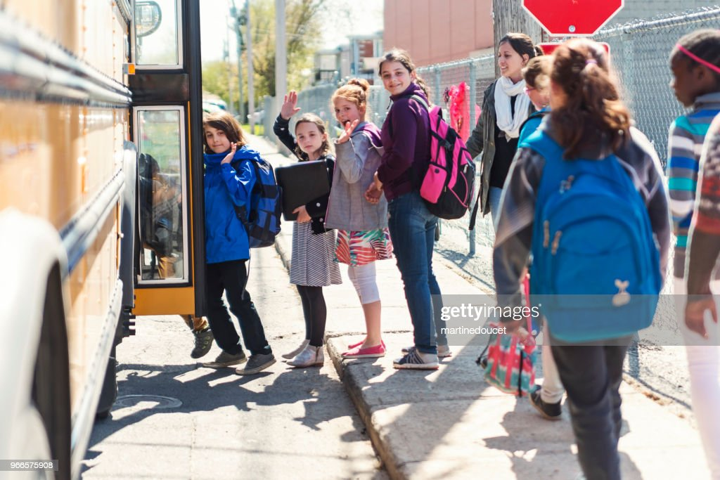 Kids in line waiting to get on school bus saying goodbye. : Stock Photo
