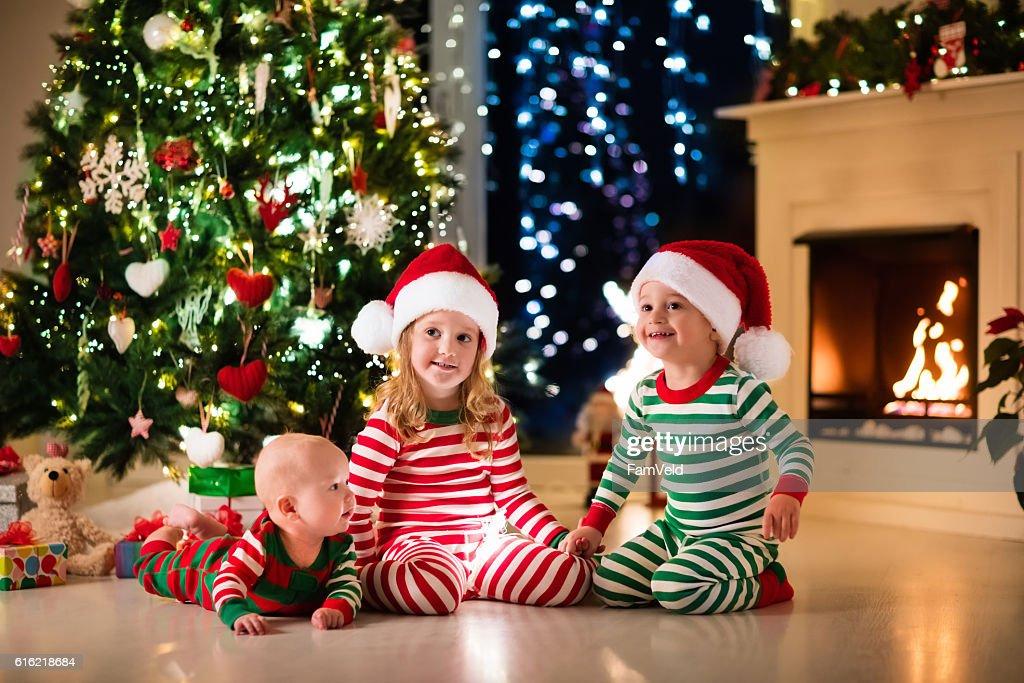 Kids in pajamas sitting under Christmas tree : Stock Photo