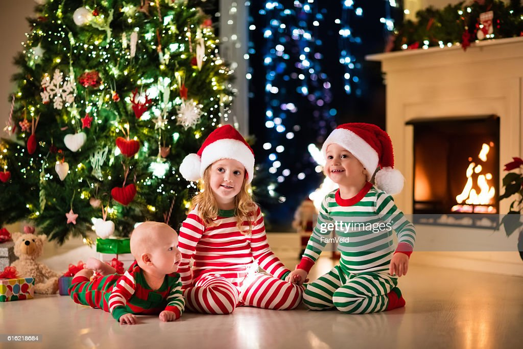 Kids in pajamas sitting under Christmas tree : ストックフォト