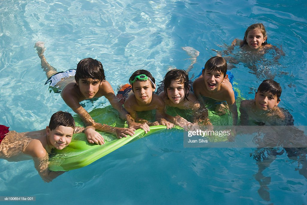 Kids (6-14) in pool with floating matress, portrait, elevated view : Foto stock