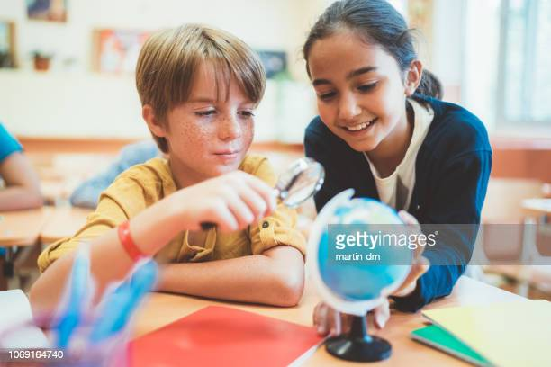 kids in school examining the globe with magnifying glass - physical geography stock pictures, royalty-free photos & images