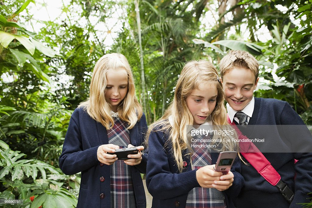 kids in school uniforms with cell phones : Stock Photo